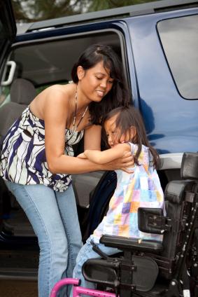 mom lifting child wheelchair